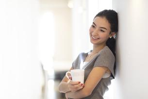 カップを持ち壁にもたれる女性の写真素材 [FYI02974136]