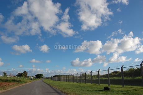 快晴の空とフェンス沿いの道の写真素材 [FYI02974582]