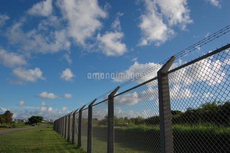 快晴の空とフェンス沿いの道の写真素材 [FYI02974589]