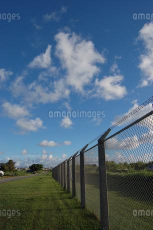 快晴の空とフェンス沿いの道の写真素材 [FYI02974590]