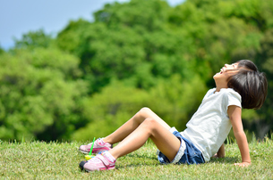 芝生広場で爆笑する女の子の写真素材 [FYI02974871]