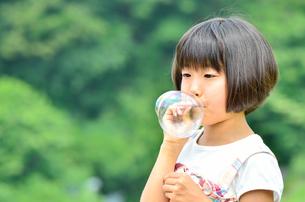 シャボン玉で遊ぶ女の子の写真素材 [FYI02974872]