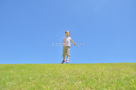 青空で走る女の子の写真素材 [FYI02974876]