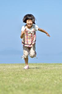 青空で走る女の子の写真素材 [FYI02974882]