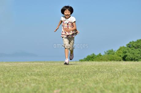 青空で走る女の子の写真素材 [FYI02974883]