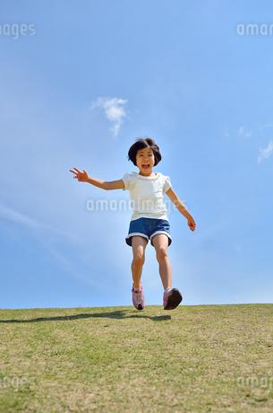 青空で走る女の子の写真素材 [FYI02974885]