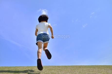 青空で走る女の子(後姿)の写真素材 [FYI02974886]