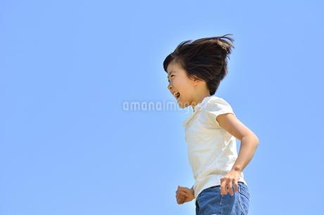 青空で走る女の子の写真素材 [FYI02974888]
