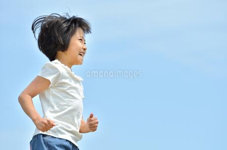 青空で走る女の子の写真素材 [FYI02974890]