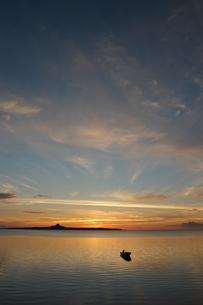 沖縄の夕日の空と穏やかな海にシルエットの和船の写真素材 [FYI02975195]