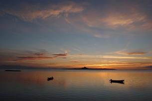沖縄の夕日の空と穏やかな海にシルエットの和船の写真素材 [FYI02975197]