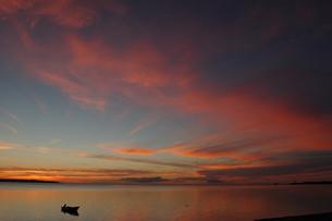 沖縄の夕日の空と穏やかな海にシルエットの和船の写真素材 [FYI02975198]