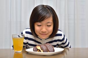 スイーツを食べる女の子(エクレア)の写真素材 [FYI02975373]