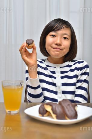 スイーツを食べる女の子(エクレア)の写真素材 [FYI02975375]