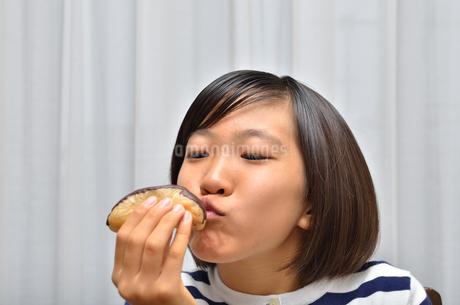 スイーツを食べる女の子(エクレア)の写真素材 [FYI02975381]