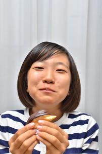 スイーツを食べる女の子(エクレア)の写真素材 [FYI02975388]