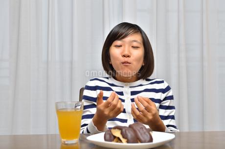 スイーツを食べる女の子(エクレア)の写真素材 [FYI02975390]