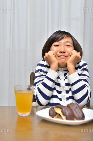 スイーツを食べる女の子(エクレア)の写真素材 [FYI02975392]