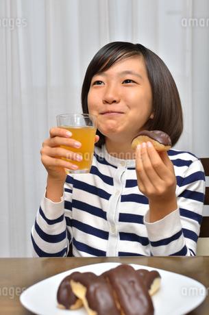 スイーツを食べる女の子(エクレア)の写真素材 [FYI02975394]
