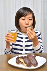 スイーツを食べる女の子(エクレア)の写真素材 [FYI02975396]