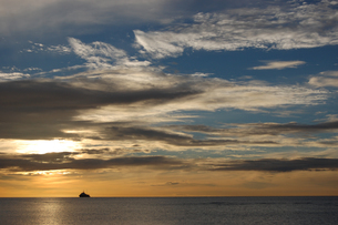 オレンジ色の夕焼けの海とシルエットの船の写真素材 [FYI02975496]