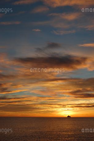 オレンジ色の夕焼けの海とシルエットの船の写真素材 [FYI02975497]