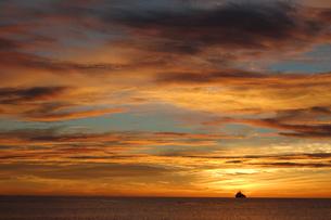 オレンジ色の夕焼けの海とシルエットの船の写真素材 [FYI02975499]