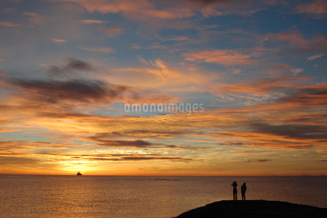 オレンジ色の夕焼けの海とシルエットの船と人の写真素材 [FYI02975504]