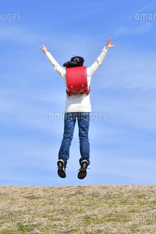 青空でジャンプする小学生の女の子(後姿)の写真素材 [FYI02975673]