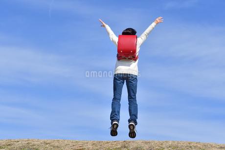 青空でジャンプする小学生の女の子(後姿)の写真素材 [FYI02975674]