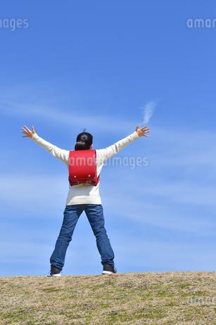 青空で両手を広げる小学生の女の子(後姿)の写真素材 [FYI02975677]