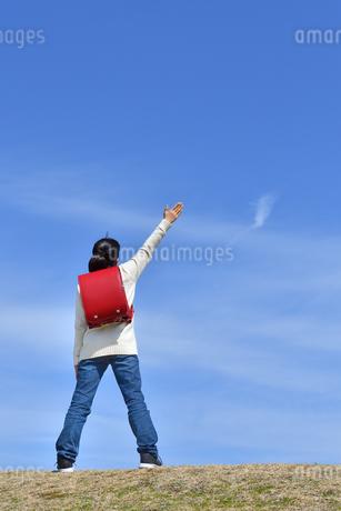 青空で手を上げる小学生の女の子(後姿)の写真素材 [FYI02975678]