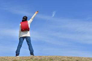 青空で手を上げる小学生の女の子(後姿)の写真素材 [FYI02975679]