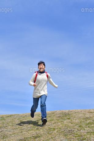 青空で走る小学生の女の子の写真素材 [FYI02975680]