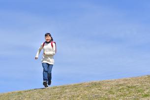 青空で走る小学生の女の子の写真素材 [FYI02975681]
