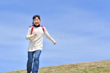 青空で走る小学生の女の子の写真素材 [FYI02975682]