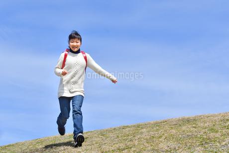 青空で走る小学生の女の子の写真素材 [FYI02975683]