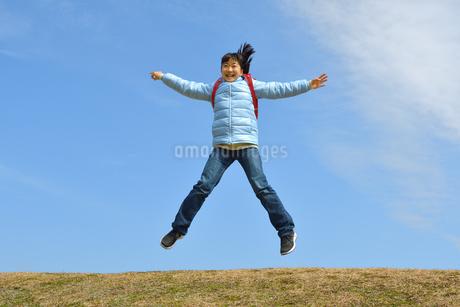 青空でジャンプする小学生の女の子(冬)の写真素材 [FYI02975688]