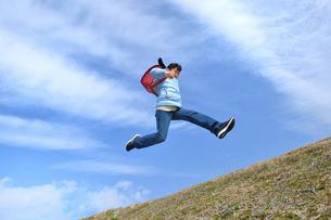 青空でジャンプする小学生の女の子(冬)の写真素材 [FYI02975691]