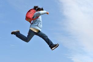 青空でジャンプする小学生の女の子(冬)の写真素材 [FYI02975693]
