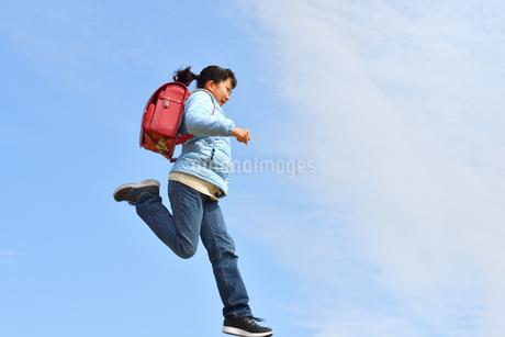 青空でジャンプする小学生の女の子(冬)の写真素材 [FYI02975695]