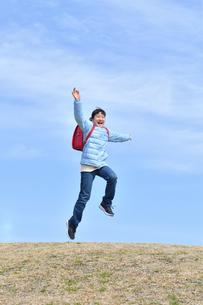 青空でジャンプする小学生の女の子(冬)の写真素材 [FYI02975699]