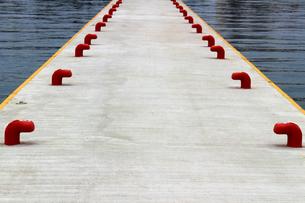 白い埠頭に並んだ赤いボラードの写真素材 [FYI02976485]