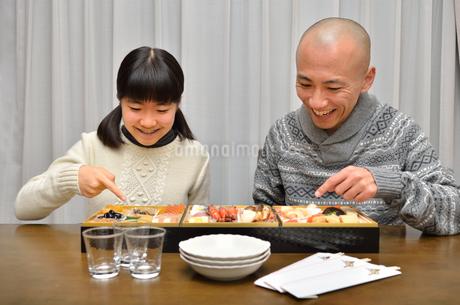 おせち料理を食べる親子の写真素材 [FYI02977162]