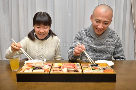 おせち料理を食べる親子の写真素材 [FYI02977166]