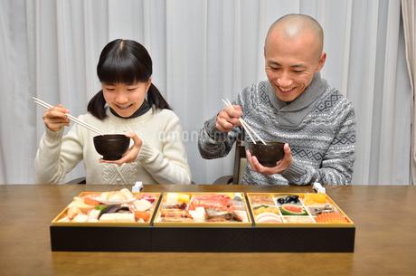 おせち料理を食べる親子の写真素材 [FYI02977169]