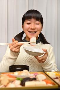 おせち料理を食べる女の子の写真素材 [FYI02977186]