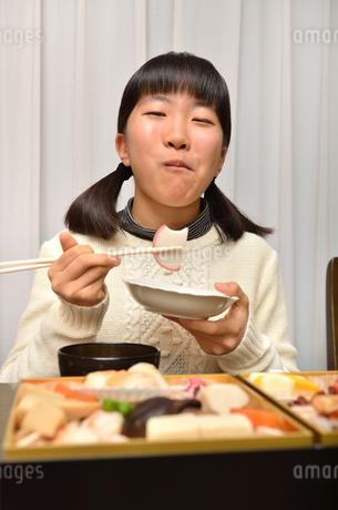 おせち料理を食べる女の子の写真素材 [FYI02977187]