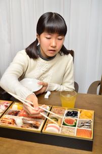 おせち料理を食べる女の子の写真素材 [FYI02977188]