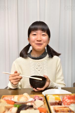 おせち料理を食べる女の子の写真素材 [FYI02977192]
